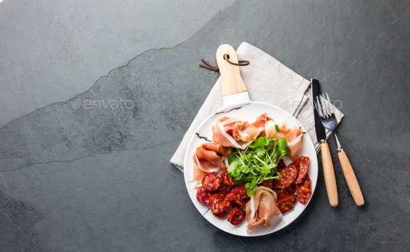Spanish ham serrano and salami on white marbled plate. Top view. Copy space. - Stock Photo - Images