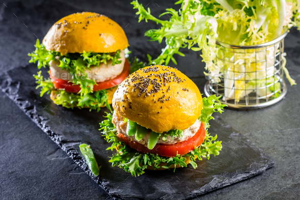 Colored yellow burgers. Chicken burgers hamburgers with turmeric bread - Stock Photo - Images