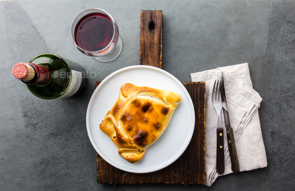 Chilean empanada served on wite plate with red wine. Top view - Stock Photo - Images