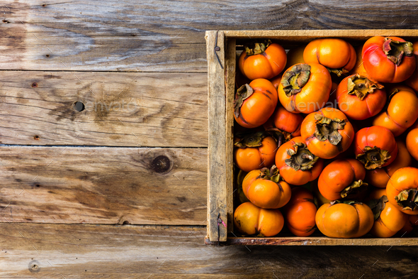 Box of fresh fruits persimmon kaki on wooden background. Copy space - Stock Photo - Images
