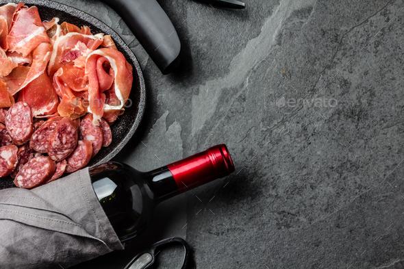 Spanish ham serrano, salami and bottle of red wine on slate - Stock Photo - Images
