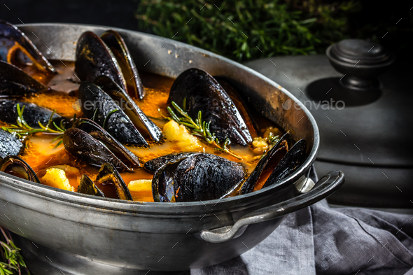 Seafood mussels tomato soup in metal pot - Stock Photo - Images
