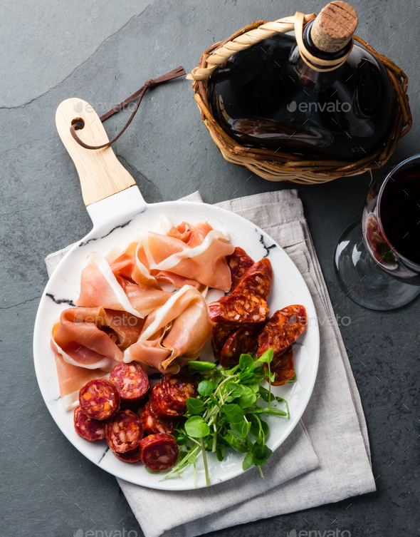 Spanish ham serrano and salami on white marbled plate an red wine. Top view. - Stock Photo - Images