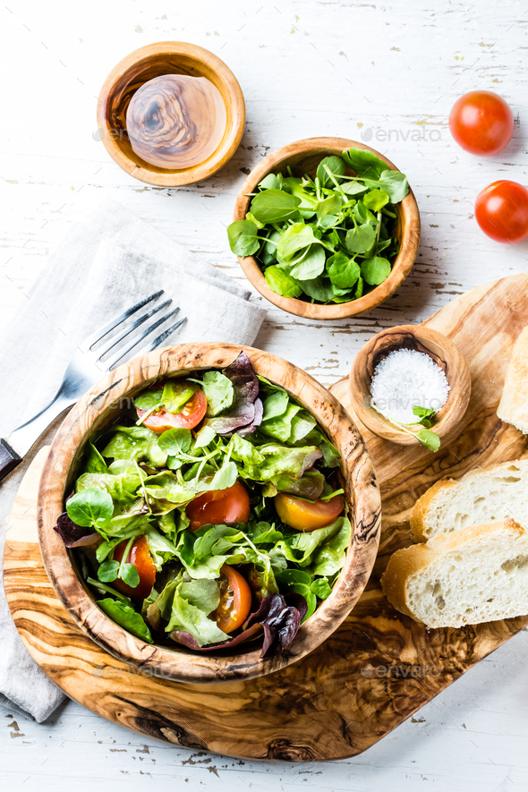 Vegetarian salad with lettuce and tomatoes in olive wooden bowl - Stock Photo - Images