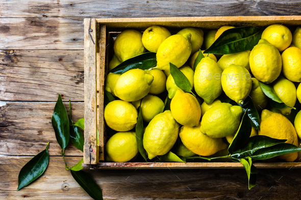 Box of lemons with fresh leaves on wooden background with copy space. Top view - Stock Photo - Images