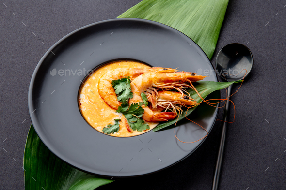 Seafood Soup decorated with whole shrimps and tropical leaves on black plate, black background - Stock Photo - Images
