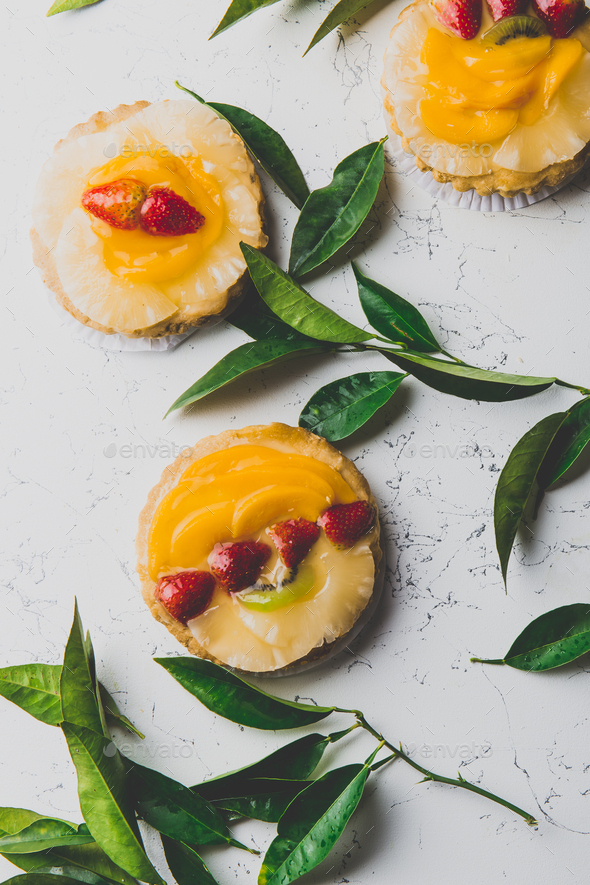 Flat lay of fruit and berry - pineaplle mango tarts and fresh leaves on white background - Stock Photo - Images