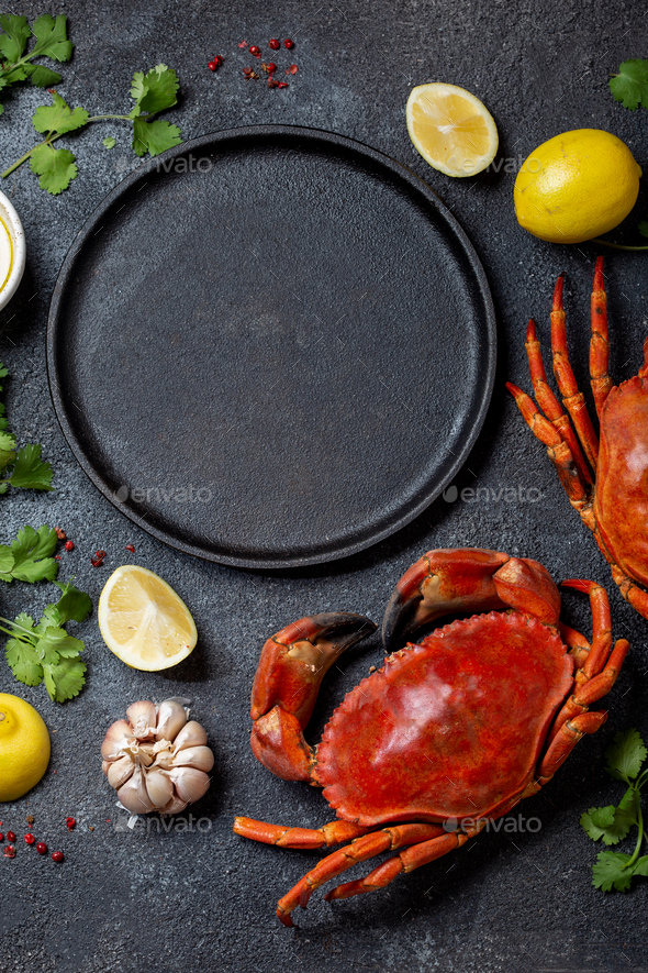 Food background with empty black plate, fresh crabs, lemons and herbs. Top view, copy space - Stock Photo - Images