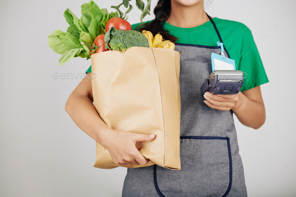Supermarket worker with bag of groceries - Stock Photo - Images