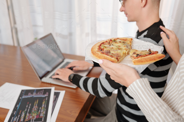 Wife bringing pizza to working man - Stock Photo - Images