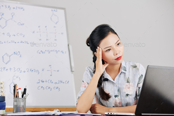 Pensive young science teacher - Stock Photo - Images