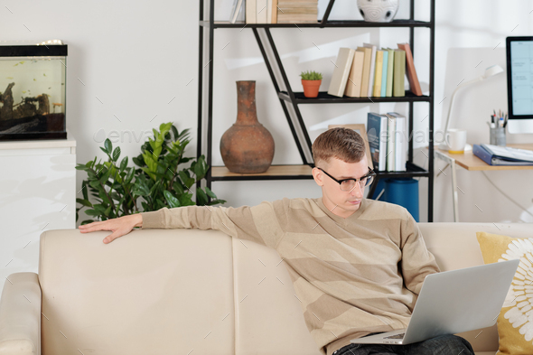Man reading document on laptop - Stock Photo - Images