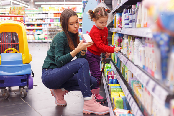 Young mom with little daughter choosing children's cosmetics at supermarket store - Stock Photo - Images