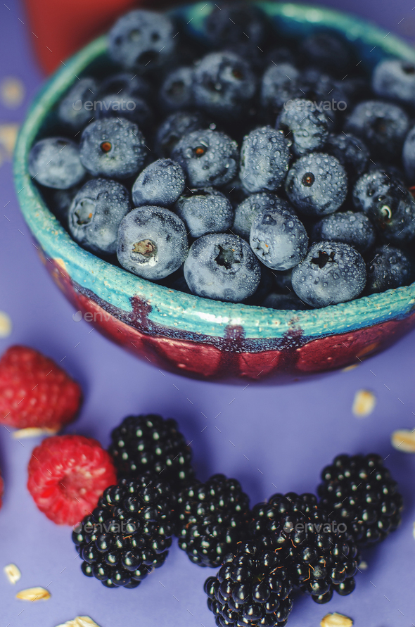 Blueberries in a plate and blackberries and raspberries on a blue background. Summer harvest. - Stock Photo - Images
