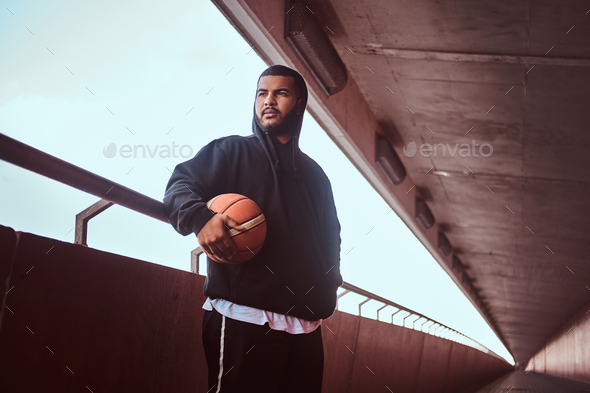 Dark-skinned guy holds a basketball while standing on a footway under bridge. - Stock Photo - Images