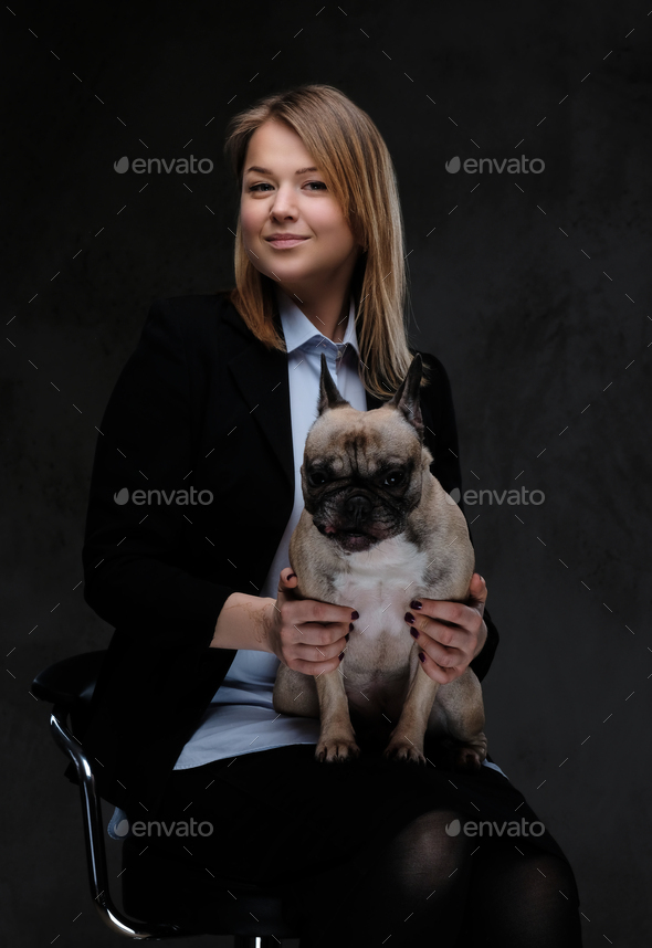 Happy blonde woman breeder sitting on a chair and holds her cute pug. - Stock Photo - Images