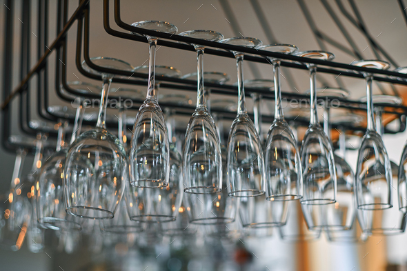 Close-up image of a wine glasses hanging in the bar above the bar counter. - Stock Photo - Images