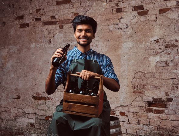Indian brewer in uniform sitting on a wooden barrel and drink craft beer. - Stock Photo - Images