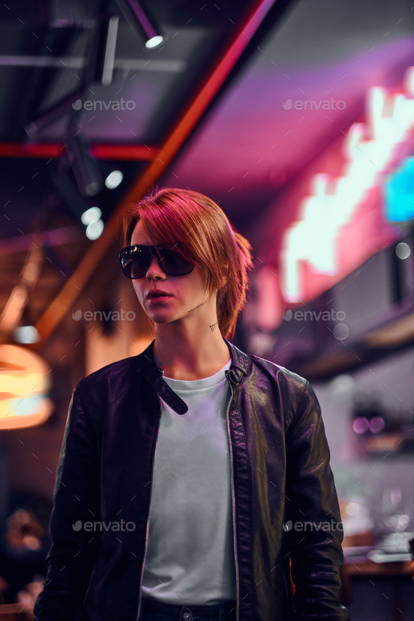 Stylish redhead girl standing in the night on the street. Illuminated signboards, neon, lights. - Stock Photo - Images