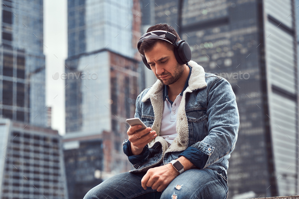 Trendy dressed male sitting in front of skyscrapers in Moscow city at cloudy morning - Stock Photo - Images