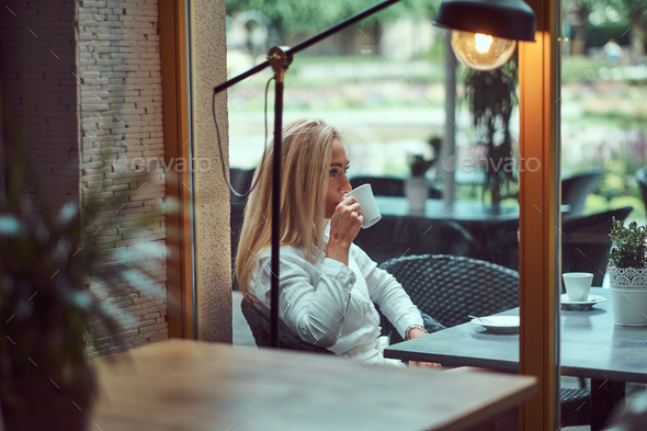 Beautiful blonde female dressed in a white blouse sitting at table drinks coffee at terrace cafe. - Stock Photo - Images