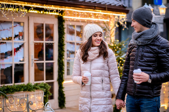 Romantic couple wearing warm clothes sitting on a bench in evening street - Stock Photo - Images