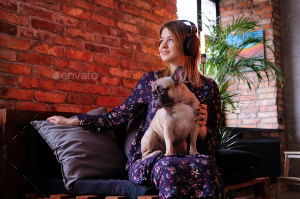 Happy blonde woman in dress sitting with her cute pug on a handmade sofa and listening to music - Stock Photo - Images
