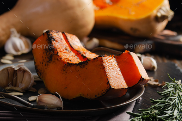 Baked pumpkin slices on metal tray on rustic kitchen wooden table - Stock Photo - Images