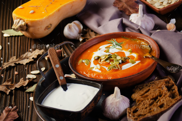 Clay dish with homemade rustic pumpkin soup with seeds on wooden table with bread and greens aside - Stock Photo - Images