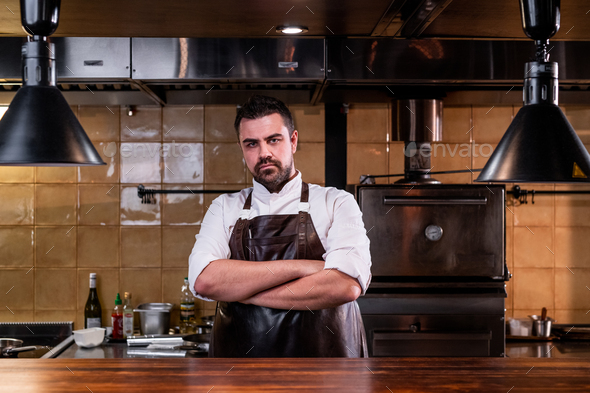 Serious chef at restaurant kitchen - Stock Photo - Images