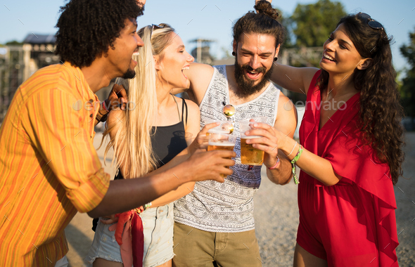 Group of happy friends hanging out and enjoying drinks, festival - Stock Photo - Images