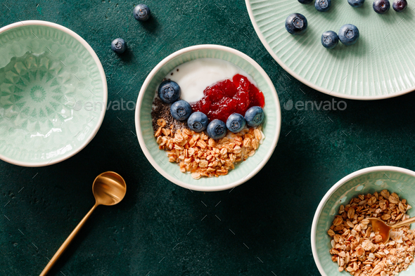 Top view of breakfast with granola, yoghurt, strawberry jam, chia seeds and blueberry - Stock Photo - Images