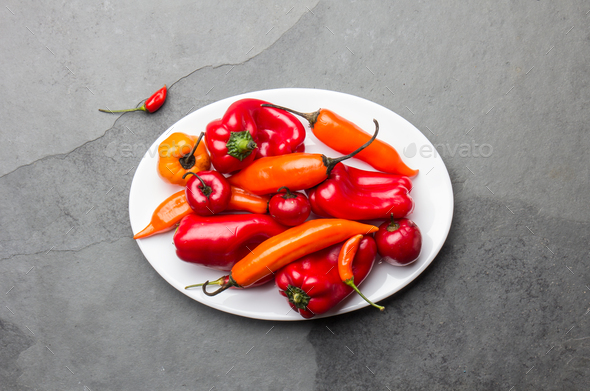 Chili and bell pepper on white plate, slate background, top view - Stock Photo - Images