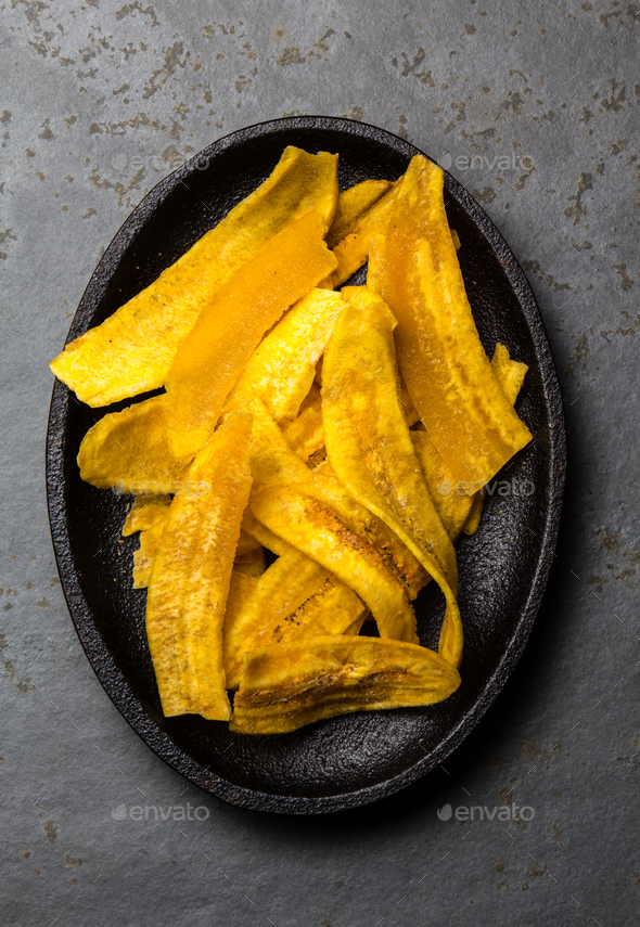 Healthy Homemade banana Plantain Chips on black plate, slate background - Stock Photo - Images