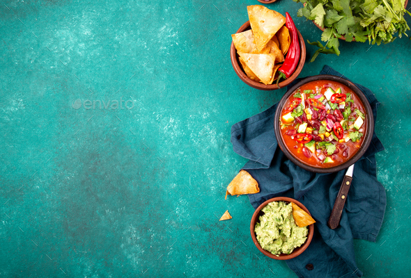 Mexican black bean soup with tomato, avocado and totopos. Blue background, top view - Stock Photo - Images
