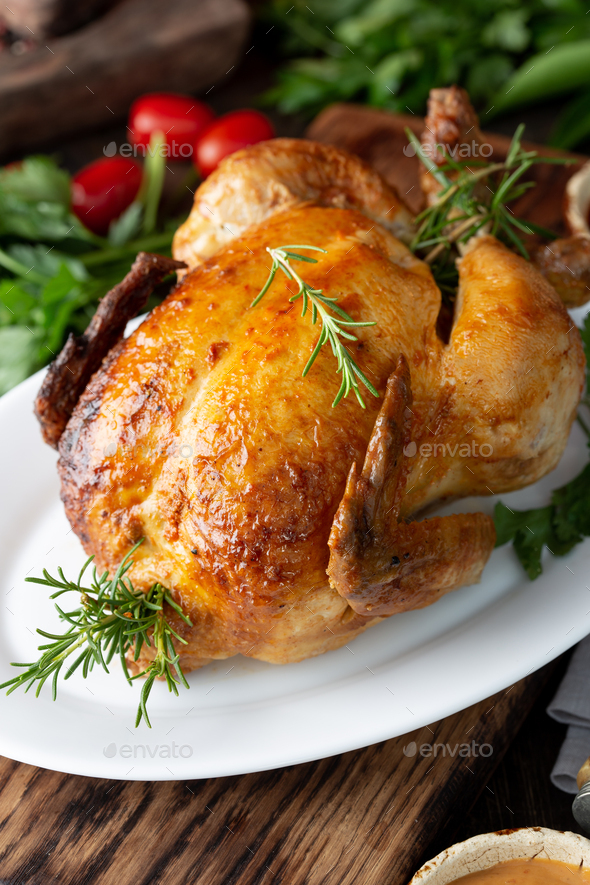 Whole Roasted Chicken on white plate with rosemary, sauces and vegetables - Stock Photo - Images