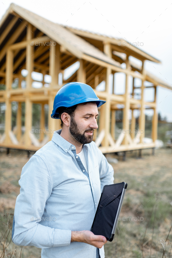 Builder near the wooden house on the construction site - Stock Photo - Images