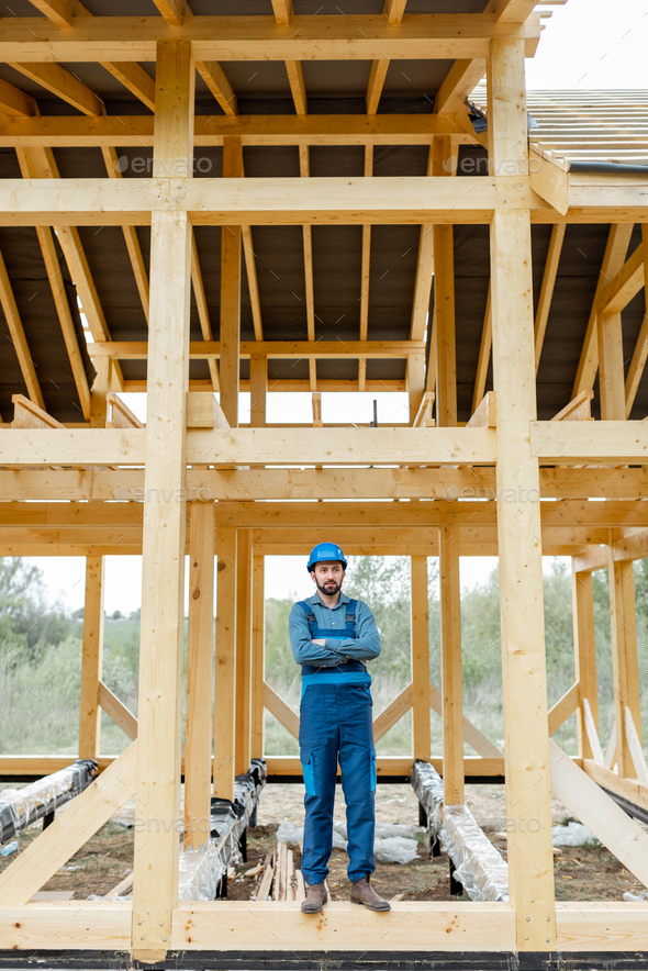 Builder on the wooden house structure on the construction site - Stock Photo - Images