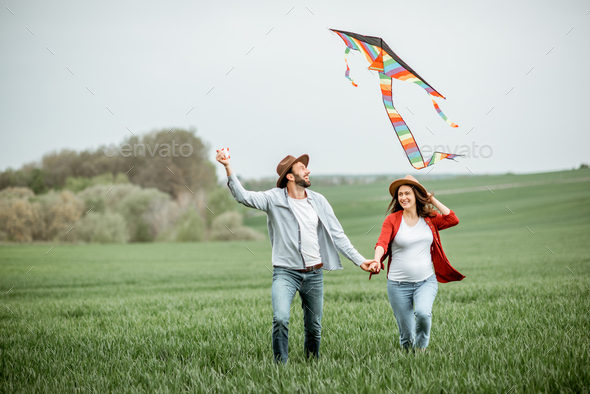 Lovely couple with kite on the greenfield - Stock Photo - Images