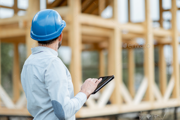 Builder with digital touchpad near the wooden house on the construction site - Stock Photo - Images