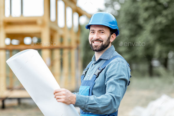 Builder with blueprints near the wooden house on the construction site - Stock Photo - Images