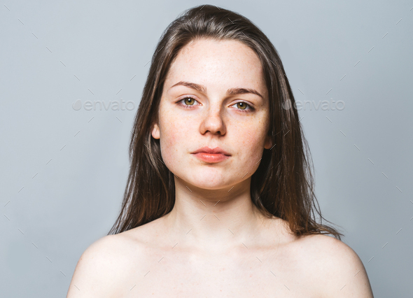 Young beautiful woman freckles natural portrait. Gray background. - Stock Photo - Images