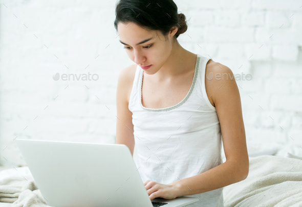 Beautiful Young Woman with Computer at home on sofa. Indoor shot. - Stock Photo - Images