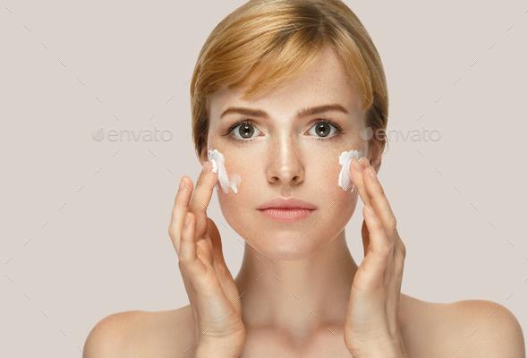 Woman beauty mask cream cosmetics skin care. Cream on cheeks. - Stock Photo - Images