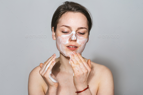 Young beautiful woman washing her face with hands by soap. Studio shot. Gray background. - Stock Photo - Images