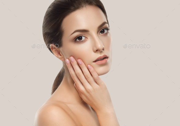 Young beautiful woman face portrait with healthy skin on gray background - Stock Photo - Images