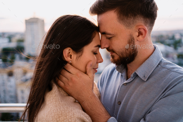 Man and woman on balcony at sunset in the city - Stock Photo - Images