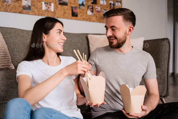 Smiling man and woman having lunch together at home - Stock Photo - Images