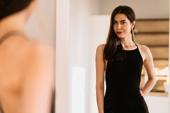 Lady wears beautiful black dress looking into the mirror - Stock Photo - Images
