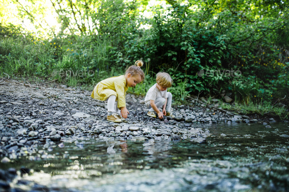 Small boy and girl playing with rocks by stream in nature - Stock Photo - Images